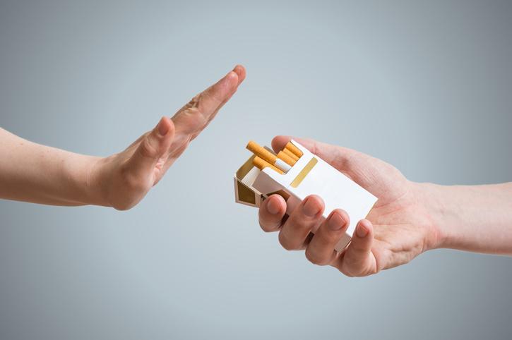 mano rechazando paquete de cigarrillos