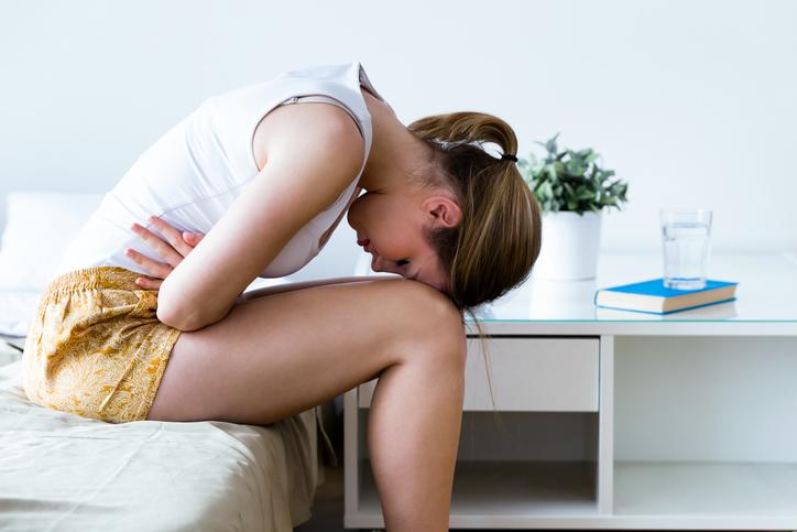 mujer joven encogida con manos sobre vientre y cabeza sobre rodilla